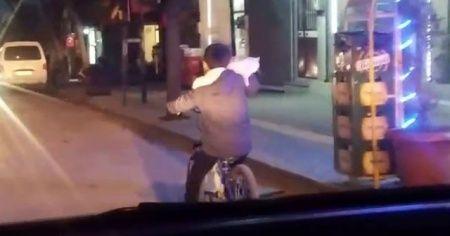 Bir eliyle kedisini tuttu, diğer eliyle bisikleti sürdü