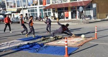 Sahası olmayan futbolcular, asfalta kilim serip antrenman yapıyor