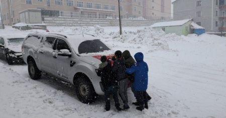 Çocuklar, bir aracın önündeki Türk bayrağının üzerindeki karı temizledi