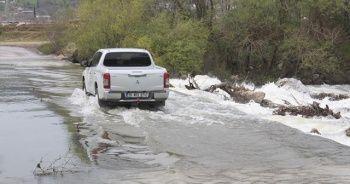 Su altında kalan köprüden tehlikeli geçiş