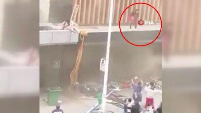 Yağmacıların ateşe verdiği binadan bebeğini atarak kurtardı