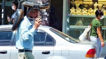 Sıcaktan alışılmışın dışında korunma yöntemi: Kafasında koltukla yürüdü
