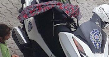 Kırık şemsiyesiyle polisin motosikletini yağmurdan korudu