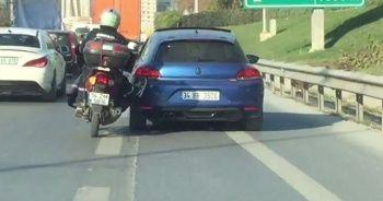 Motosiklet sürücüsü yolda kalan aracı ayaklarıyla itti