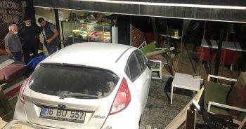 Otomobil dükkana dalıp merdivenlerde asılı kaldı