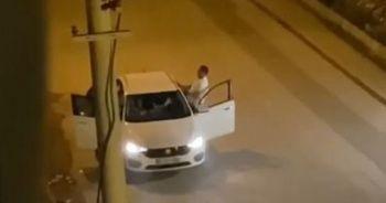 Ayırmaya çalışanlara rağmen araç içindeki kadına tekme attı